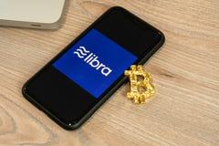 18 de junio de 2019, Ljubljana Eslovenia - smartphone con el logotipo del libra en él, al lado de la moneda de Bitcoin El nuevo g fotos de archivo