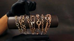 De juwelen in de opslag, in zwarte handschoenen wordt verkocht tonen gouden juwelen in de opslag, heel wat gouden armbanden, kett stock footage