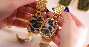 De juwelen in een wijfje overhandigen, de oorringen van de vrouwenholding, macrovideo stock video