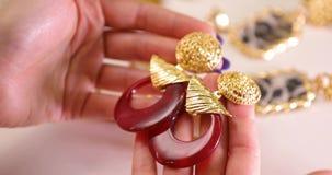 De juwelen in een wijfje overhandigen, de oorringen van de vrouwenholding, macrovideo stock videobeelden