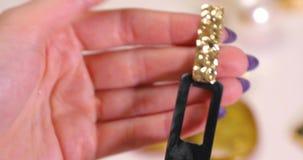 De juwelen in een wijfje overhandigen, de oorringen van de vrouwenholding, macrovideo stock footage