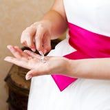 De juwelen van de bruidholding in haar handen Stock Foto