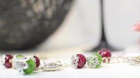 De juwelenhalsband of de armband van rood en groen met metaal nemen een vrouwelijke hand op stock videobeelden