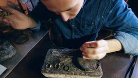 De juwelier maakt een stuk van juwelen De mannelijke juwelier verwarmt een zilveren ketting stock videobeelden