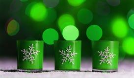 De kaarsen die zich in sneeuw bevinden met defocussed feelichten, groene bokeh op de achtergrond, Feestelijke Kerstmisachtergrond Stock Foto