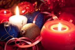 De kaarsen en de snuisterijen van Kerstmis op rood Stock Afbeeldingen