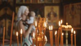 De kaarsen is op de voorgrond, moeder met baby op vage achtergrond in kerk stock video