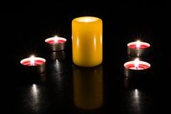 De kaarsen steken op de lijst, donkere achtergrond aan royalty-vrije stock afbeelding