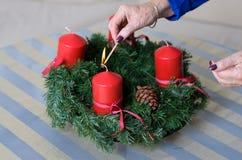 De kaarsen van de vrouwenverlichting op een Kerstmiskroon Stock Foto