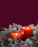 De kaarsen van Kerstmis op een rode achtergrond Ruimte voor tekst Stock Afbeelding