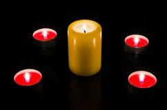 De kaarsen worden aangestoken op de lijst, donkere achtergrond Toppmening stock afbeelding
