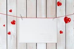 De kaart van de de daggroet van Valentine op rode die draden door harten op houten witte achtergrond worden omringd royalty-vrije stock foto's
