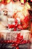 De kaart van de Kerstmisgroet met giftdozen met een rood lint, vogel worden gebonden bij glanst vakantiedecoratie en bokeh verlic Stock Fotografie