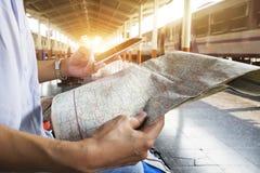 De kaart van de reizigersholding, wachten voor een trein bij station en het schaven voor volgende reis door mobilofoon Royalty-vrije Stock Afbeeldingen