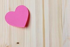 De kaart van de valentijnskaartendag met kleverige nota in de vorm van een hart op een houten achtergrond Royalty-vrije Stock Afbeeldingen