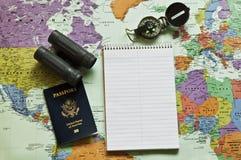 De kaart van de wereld met blocnote, paspoort, omringt stock afbeeldingen
