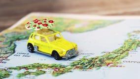 De kaart van Japan met een gele keverstuk speelgoed auto met een witte paraplu stock video