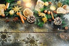 De kaart van de Kerstmisgroet met giften, kaars, kegels, pijpjes kaneel, droge oranje, groene boom over oude donkere houten achte Stock Afbeeldingen