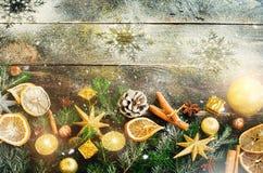 De kaart van de Kerstmisgroet met giften, kaars, kegels, pijpjes kaneel, droge oranje, groene boom over oude donkere houten achte Stock Foto's