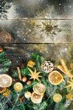 De kaart van de Kerstmisgroet met giften, kaars, kegels, pijpjes kaneel, droge oranje, groene boom over oude donkere houten achte Royalty-vrije Stock Foto