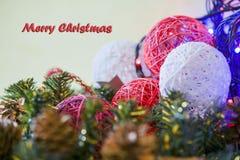 De kaart van de Kerstmisgroet op houten brandende kaars als achtergrond, rode Kerstmisballen en groene takkerstboom Stock Fotografie
