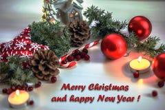 De kaart van de Kerstmisgroet op houten brandende kaars als achtergrond, rode Kerstmisballen en groene takkerstboom Stock Foto