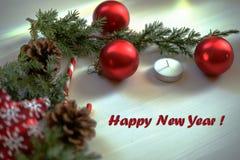 De kaart van de Kerstmisgroet op houten brandende kaars als achtergrond, rode Kerstmisballen en groene takkerstboom Royalty-vrije Stock Afbeeldingen