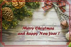 De kaart van de Kerstmisgroet op houten brandende kaars als achtergrond, rode Kerstmisballen en groene takkerstboom Stock Foto's