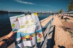 De kaart van Riga van de meisjesholding in handen Stock Afbeeldingen