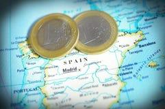De kaart van Spanje en Euro muntstukken stock afbeelding