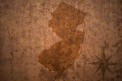 De kaart van de staat van New Jersey op een oude uitstekende document achtergrond royalty-vrije stock fotografie