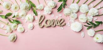 De kaart van de de Valentijnskaartendag van heilige met ranunculus bloemen en woordliefde stock foto's