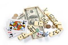 De kaarten, dobbelen, domino's en geld op een witte achtergrond Stock Foto's