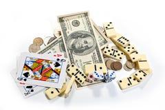De kaarten, dobbelen, domino's en geld op een witte achtergrond Stock Afbeelding