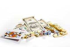 De kaarten, dobbelen, domino's en geld op een witte achtergrond Royalty-vrije Stock Fotografie