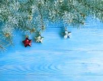 De kaartgrens van de kerstboomtak op blauwe houten achtergrond, sneeuw royalty-vrije stock foto's