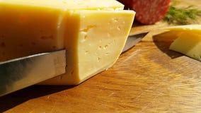 De kaas van messenolievlekken op een houten raad, het slow-motion schieten, greens, worstsalami stock video