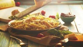 De kaas wordt geraspt op de plaat van vers-gekookte Italiaanse deegwaren stock videobeelden