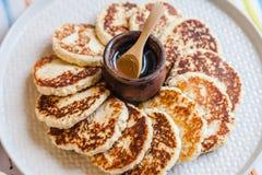 De Kaaspannekoeken van het ochtendontbijt en een juskom met honing stock foto's