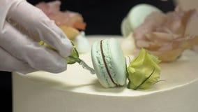 De kaastaart is bak met kalkkoekjes wordt verfraaid en de bloemen die, sluiten omhoog stock videobeelden