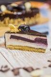 De kaastaart wordt gegoten met chocolade en bessentussenlaag Stock Foto