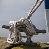 De kabel van de bootmeertros rond meerpaal wordt gebonden die stock foto