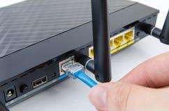 De kabel van Internet van mensenstoppen in de router Stock Foto
