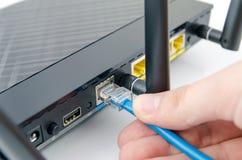 De kabel van Internet van mensenstoppen in de router Stock Fotografie