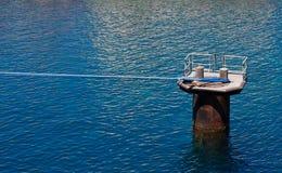 De Kabel van schepen die aan Post in Blauw Water wordt gebonden Stock Foto