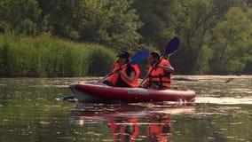De kajak met een kerel en een meisje zwemt op de rivier Langzame Motie stock videobeelden