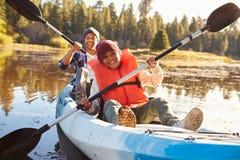 De Kajak van vaderand son rowing op Meer stock afbeeldingen