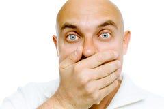 De kale bang gemaakte mens in een wit jasje behandelt haar mond met van hem Stock Afbeelding