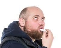 De kale Gebaarde Vette Mens gebruikt een Beschermende Lippenstift Stock Fotografie