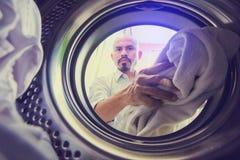 De kale mens met snor brengt kleren of stof binnen aan w stock fotografie